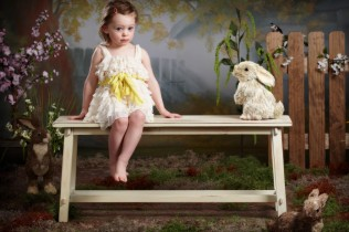 fine art portrait of girl in dress with easter bunny on a bench