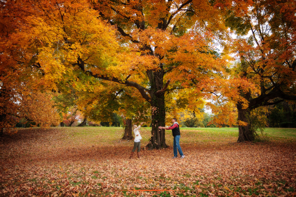 Engagement session in a park during the fall foliage. The couple is playing and throwing leaves in the air.