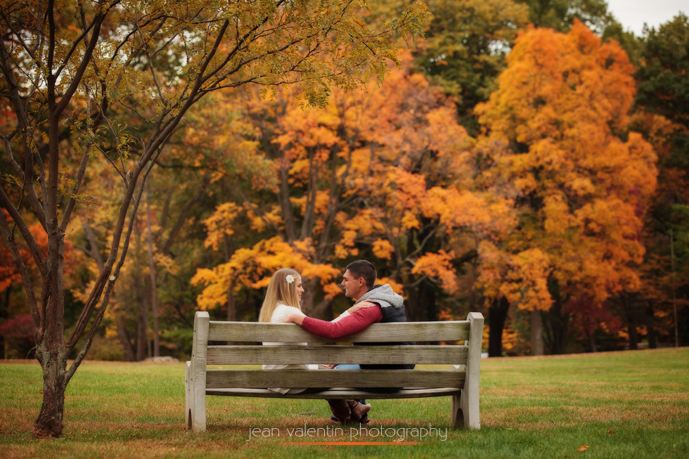 Couple sitting on a bench with beautiful fall foliage in the background